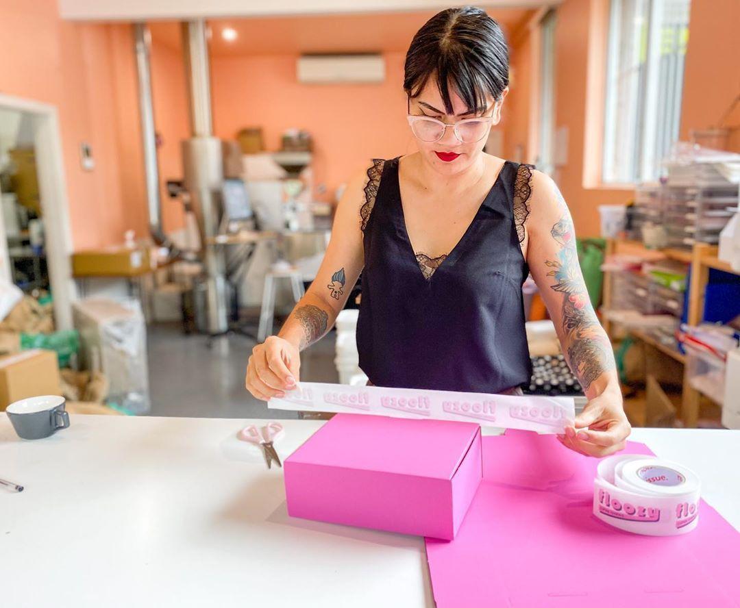 Woman applying tape to box